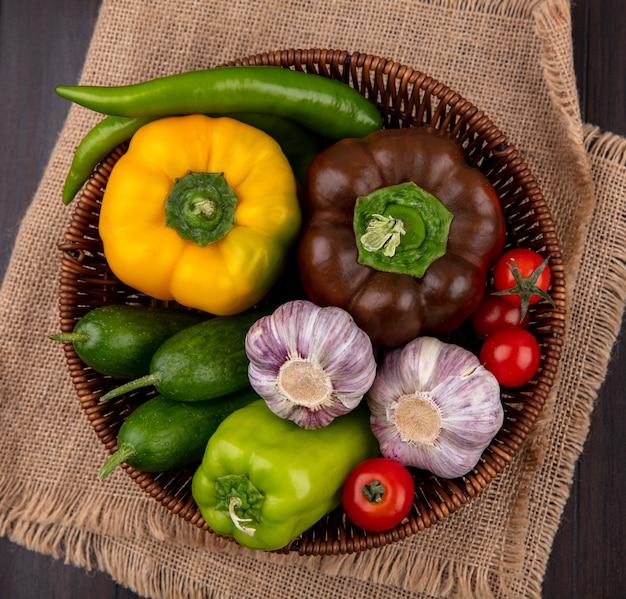 Bovenaanzicht van groenten als peper komkommer knoflook in mand op zak en houten oppervlak