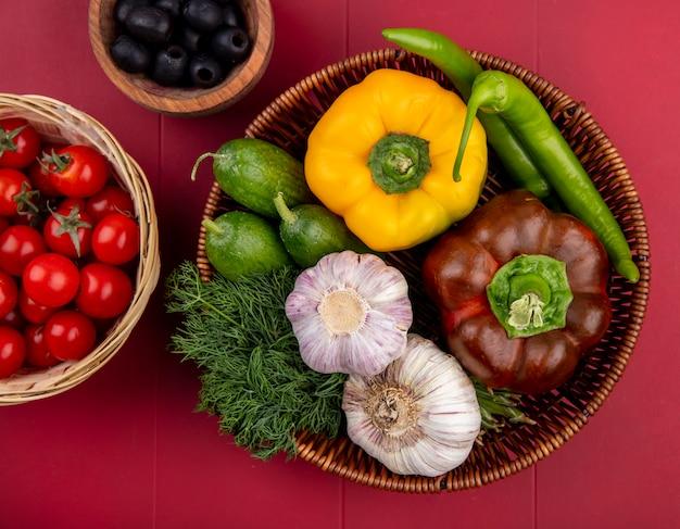 Bovenaanzicht van groenten als peper komkommer tomaat knoflook dille met olijfolie in manden op rode ondergrond