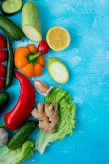 Bovenaanzicht van groenten als pepersla gember en anderen aan de linkerkant op blauw oppervlak