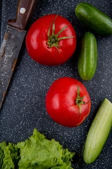 Bovenaanzicht van groenten als sla van de tomatenkomkommer met mes op snijplank als oppervlak