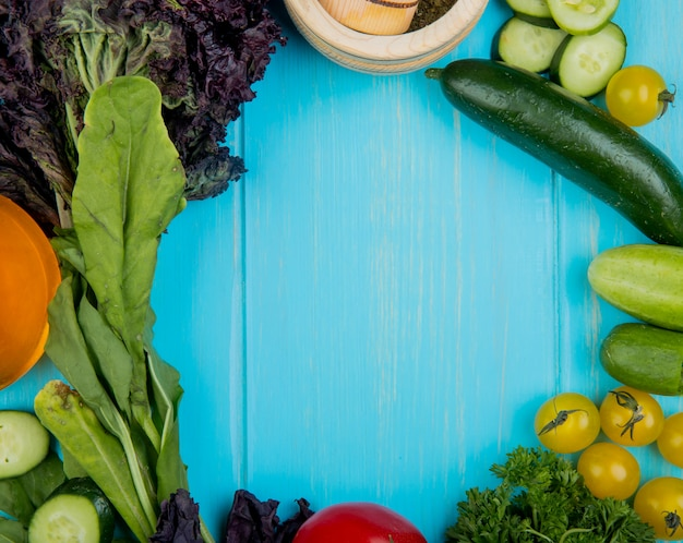 Bovenaanzicht van groenten als spinazie basilicum komkommer tomaten koriander met knoflook crusher op blauw met kopie ruimte