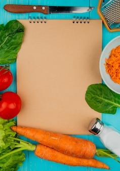 Bovenaanzicht van groenten als spinazie tomaten wortel sla met zout mes metalen rasp met notitieblok op blauwe achtergrond met kopie ruimte