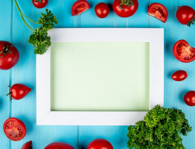 Bovenaanzicht van groenten als tomaat en koriander rond bord op blauw oppervlak met kopie ruimte