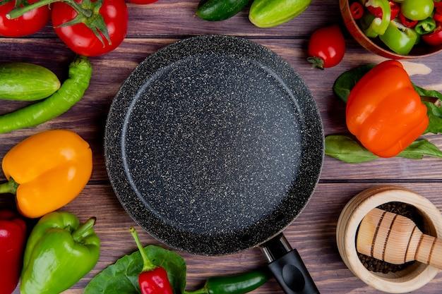 Bovenaanzicht van groenten als tomaat komkommer peper met bladeren en zwarte peper in knoflook crusher en koekenpan op hout