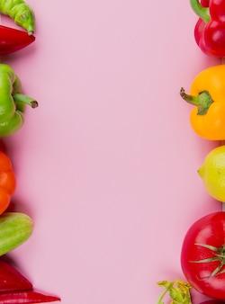 Bovenaanzicht van groenten als tomaat peper komkommer op paars met kopie ruimte