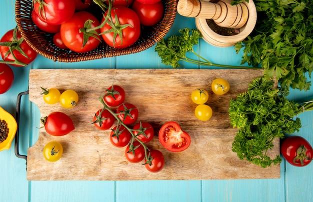 Bovenaanzicht van groenten als tomaten koriander op snijplank met knoflook crusher zwarte peper op blauw