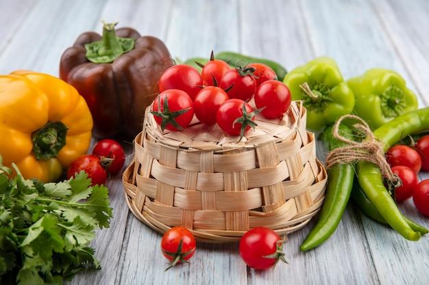 Bovenaanzicht van groenten als tomaten op mand met koriander pepers en tomaten rond op houten oppervlak