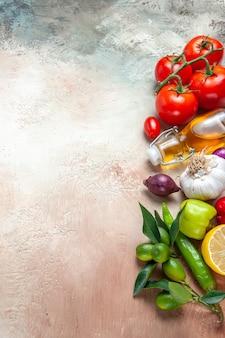 Bovenaanzicht van groenten, citrusvruchten, knoflook, paprika, citroenolie, ui, tomaten