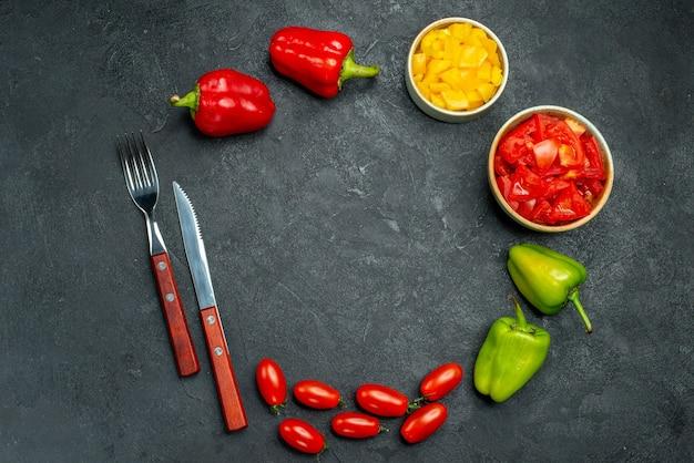 Bovenaanzicht van groenten en bestek met vrije plek voor tekst in het midden op donkergrijze tafel