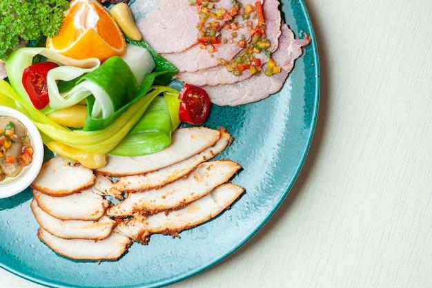 Bovenaanzicht van groenten en gekruid vlees op blauw bord