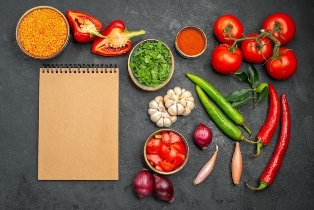 Bovenaanzicht van groenten linze in kom naast de kleurrijke groenten en kruiden notebook