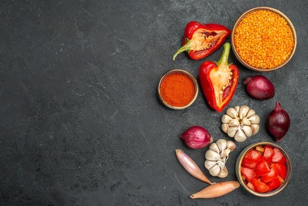 Bovenaanzicht van groenten, linzen, kruiden, tomaten, knoflook, ui, paprika