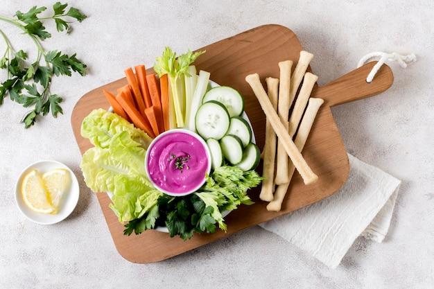 Bovenaanzicht van groenten met roze saus op snijplank