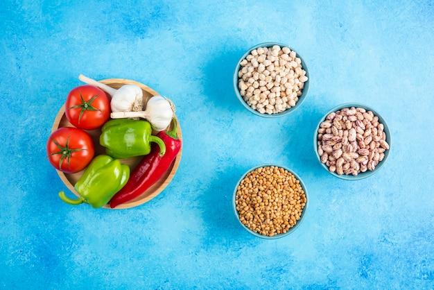 Bovenaanzicht van groenten op een houten bord en graanproducten.
