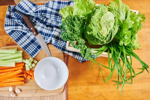 Bovenaanzicht van groenteset bestaande uit gehakte wortelen, komkommer op een houten bord, bladsla, groene uien en kom