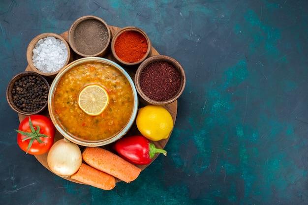 Bovenaanzicht van groentesoep met citroen, kruiden en verse groenten op donkerblauwe ondergrond