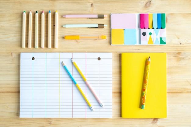 Bovenaanzicht van groep kleurpotloden, pennen, gummen en boek in felgele kaft met gelinieerd vel papier en potloden in de buurt