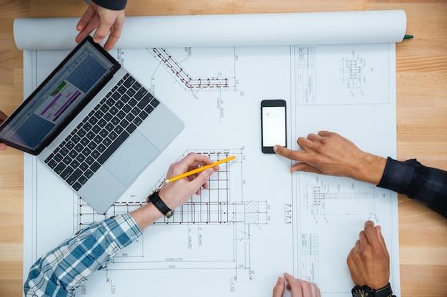 Bovenaanzicht van groep mensen die werken met laptop, smartphone en blauwdruk