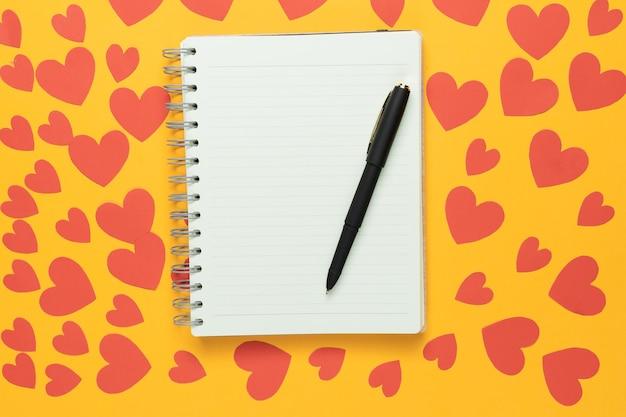 Bovenaanzicht van grote lege spiraalvormige blocnote op gele achtergrond. veel rode papieren harten