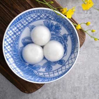 Bovenaanzicht van grote tangyuan yuanxiao (kleefrijst knoedelballen) voor eten van het nieuwe maanjaarfestival, woorden op de gouden munt betekenen de naam van de dynastie die het heeft gemaakt.