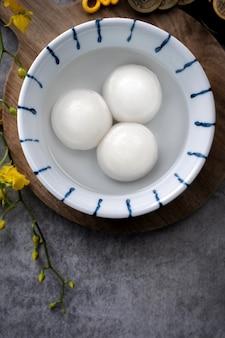 Bovenaanzicht van grote tangyuan yuanxiao (kleefrijst knoedelballen) voor maannieuwjaarsfestivalvoedsel, woorden op de gouden munt betekenen de naam van de dynastie die het heeft gemaakt.