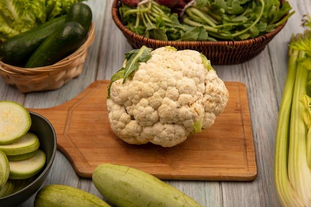 Bovenaanzicht van grote witte en ronde plantaardige bloemkool op een houten keukenbord met gehakte courgettes op een kom met komkommers en sla op een emmer met selderij en courgettes