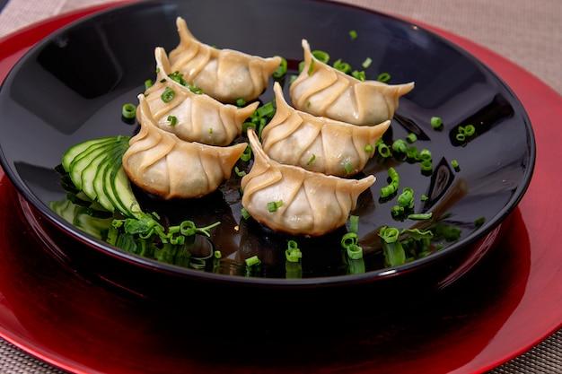 Bovenaanzicht van gyoza-gerecht, japans eten dim sum, aziatisch vers voedsel met groenten op een zwarte schotel