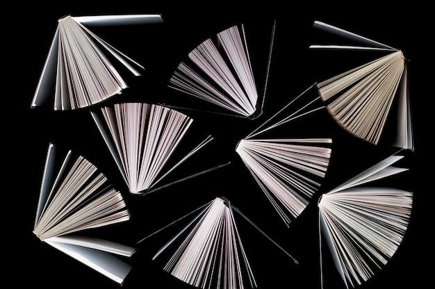 Bovenaanzicht van half geopende boeken op zwart