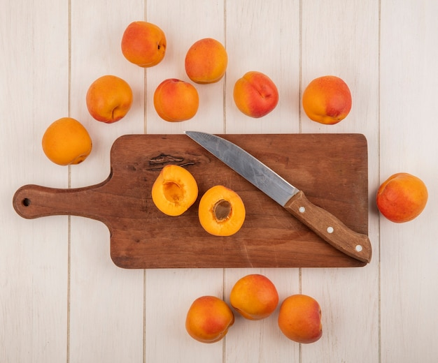 Bovenaanzicht van half gesneden abrikoos met mes op snijplank en patroon van abrikozen op houten achtergrond