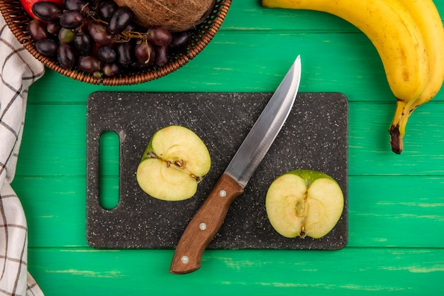 Bovenaanzicht van half gesneden appel en mes op snijplank met mandje van druivenmost kokos op geruite doek en banaan op groene achtergrond