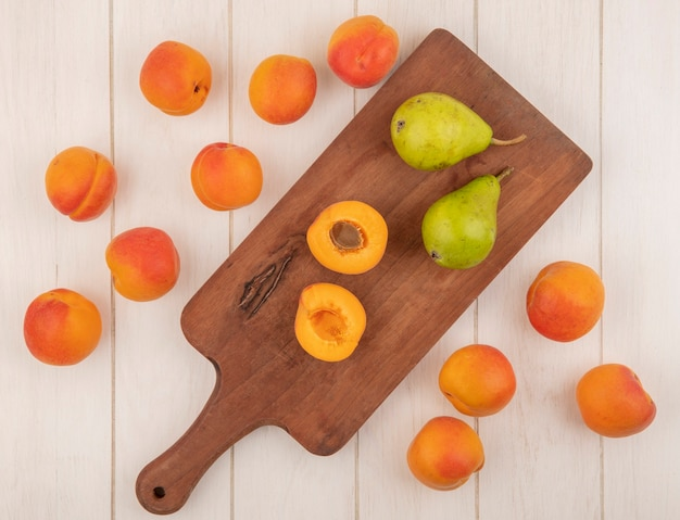 Bovenaanzicht van half gesneden en hele vruchten als abrikoos en peren op snijplank en patroon van abrikozen op houten achtergrond