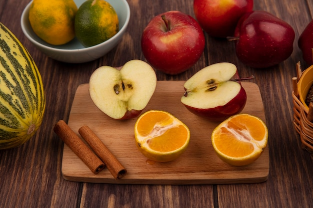 Bovenaanzicht van half smakelijke appels op een houten keukenbord met halve mandarijnen en kaneelstokjes met kantaloepmeloen met appels geïsoleerd op een houten muur