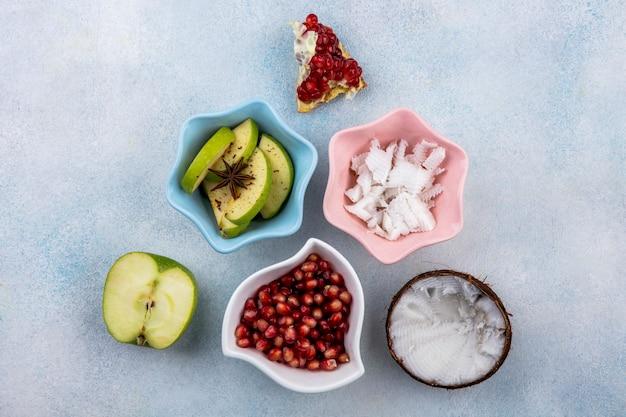 Bovenaanzicht van half verse kokosnoot met vruchtvlees van kokos in een roze kom appelschijfjes en granaatappelzaden in een witte kom op wit oppervlak