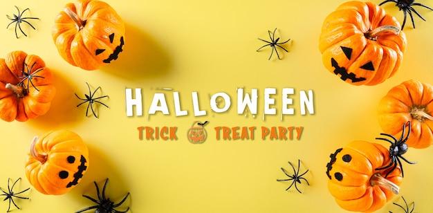 Bovenaanzicht van halloween ambachten, oranje pompoen, spook, vleermuis en zwarte spin op pastel gele achtergrond. plat lag, top uitzicht met halloween-tekst.