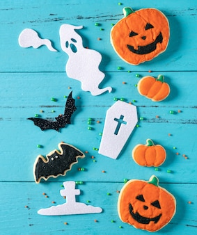 Bovenaanzicht van halloween feestelijk versierde gebakken glazuur peperkoek suiker koekjes op blauwe achtergrond met kopie ruimte en plat lag.