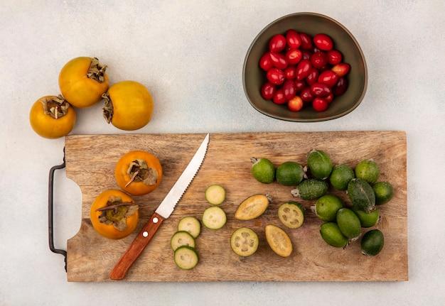 Bovenaanzicht van halve en hele feijoas op een houten keukenbord met kaki met mes met cornelian kersen op een kom op een grijze ondergrond