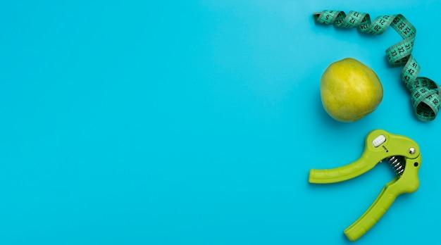 Bovenaanzicht van hand grijper met appel en meetlint