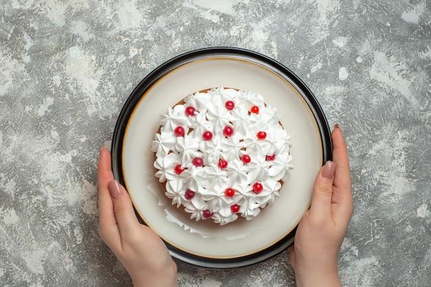 Bovenaanzicht van hand met een bord met heerlijke romige cake versierd met fruit op ijsachtergrond