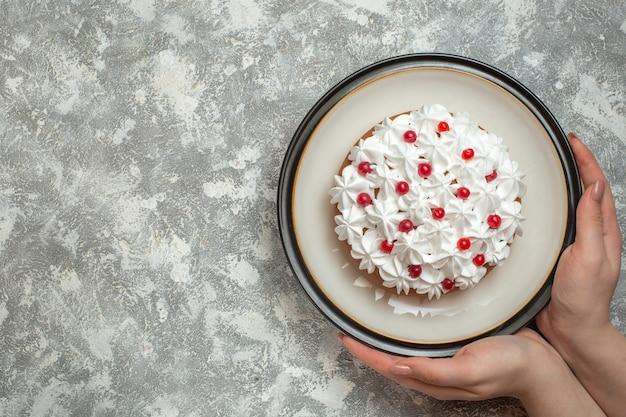 Bovenaanzicht van hand met een bord met heerlijke romige cake versierd met fruit