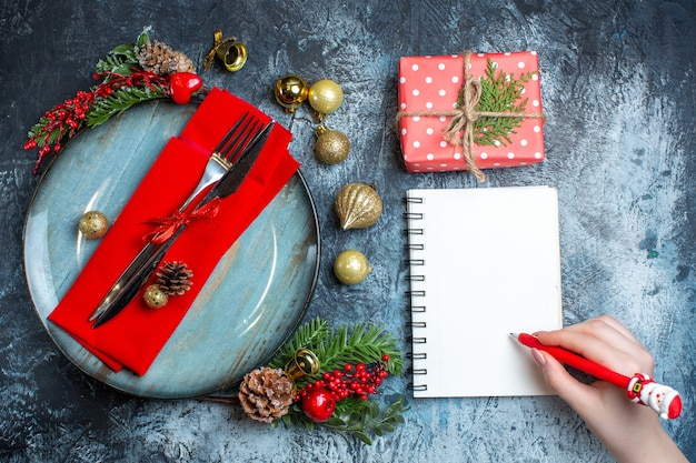 Bovenaanzicht van hand met een pen op spiraalvormig notitieboekje en geschenkdoos naast bestekset