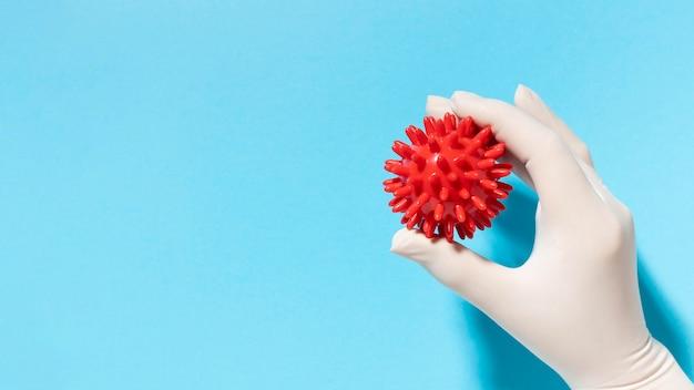 Bovenaanzicht van hand met handschoen met virus met kopie ruimte