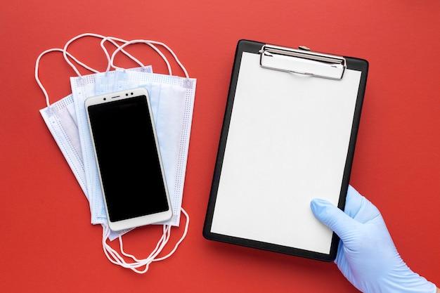 Bovenaanzicht van hand met klembord met medische maskers en smartphone
