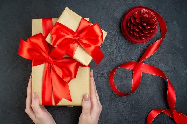 Bovenaanzicht van hand met mooie geschenken en conifer kegel op donkere achtergrond