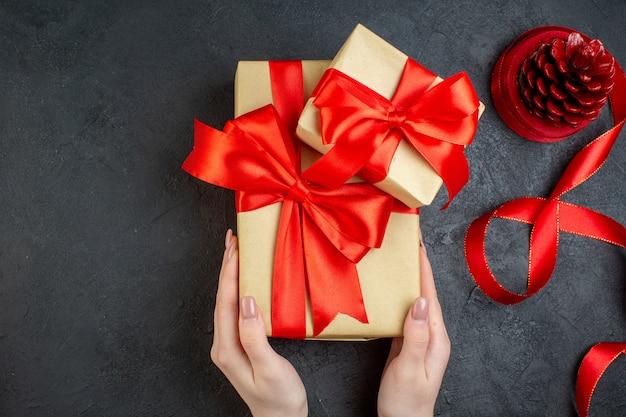 Bovenaanzicht van hand met mooie geschenken en coniferen kegel aan de rechterkant op donkere achtergrond