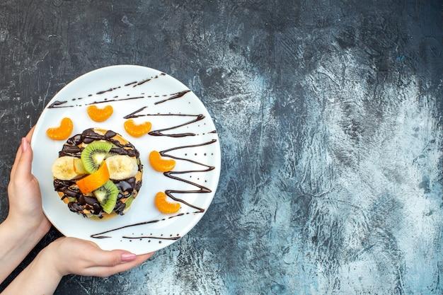 Bovenaanzicht van hand met pannenkoeken in amerikaanse stijl gemaakt met natuurlijke yoghurt en gestapeld met lagen fruit versierd met chocolade op witte plaat