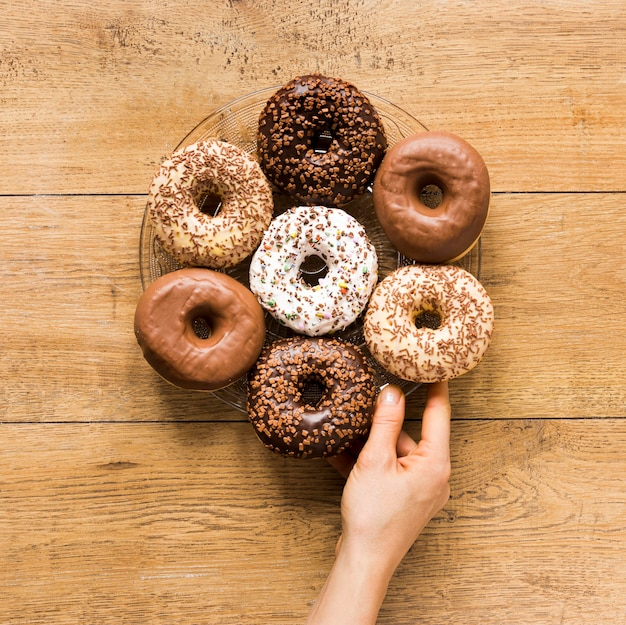 Bovenaanzicht van hand met plaat met verschillende donuts