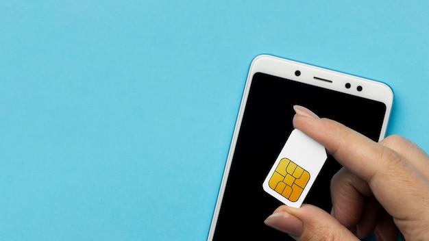 Bovenaanzicht van hand met simkaart met smartphone en kopie ruimte