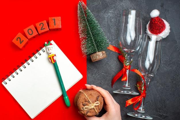 Bovenaanzicht van hand met spiraal notebook en kerstboom glazen bekers nummers hand met gestapelde koekjes op donkere en rode achtergrond