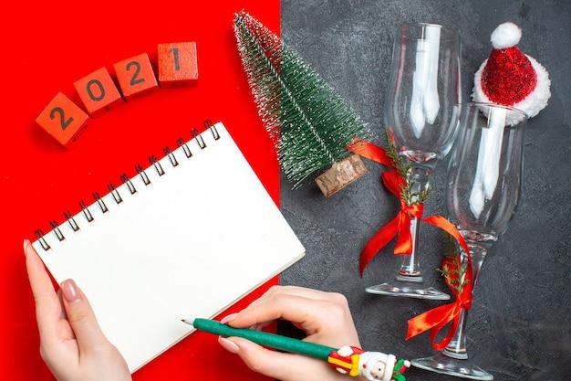 Bovenaanzicht van hand met spiraal notebook en kerstboom glazen bekers nummers op donkere en rode achtergrond