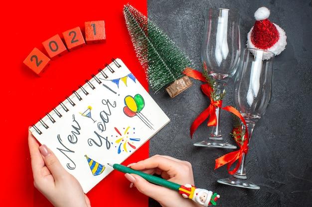 Bovenaanzicht van hand met spiraal notebook met nieuwjaarstekening en kerstboom glazen bekers nummers op donkere en rode achtergrond